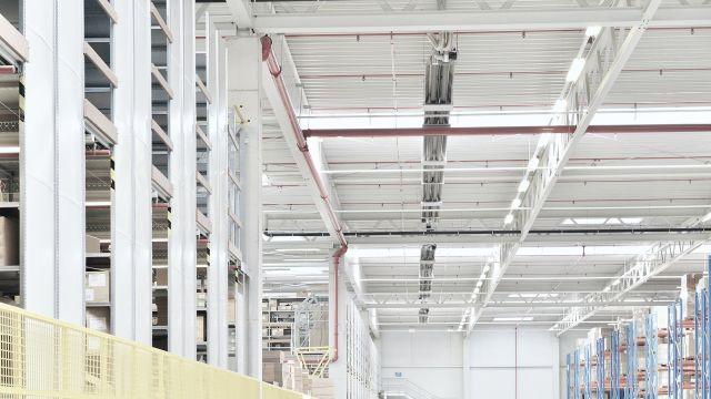 Lange Reihe an Dunkelstrahlern von Schwank in einem Logistikzentrum.